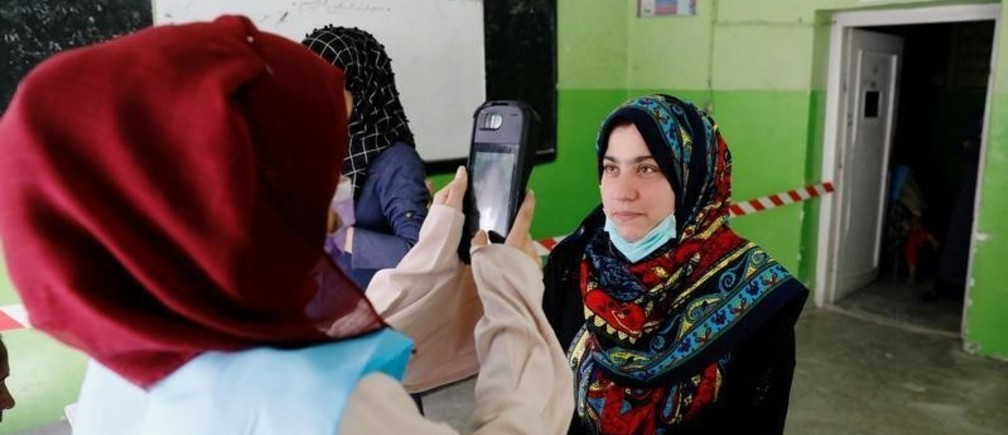 An election worker takes a picture by biometric device in the presidential election in Kabul, Afghanistan September 28, 2019. REUTERS/Mohammad Ismail - RC19AC7C7940