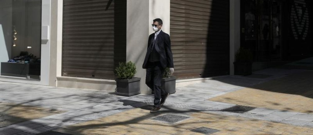 A man wears a protective face mask as he walks outside a closed store, as a precaution against the spread of the coronavirus disease (COVID-19), in Athens, Greece, March 18, 2020. REUTERS/Costas Baltas - RC2EMF979L5T