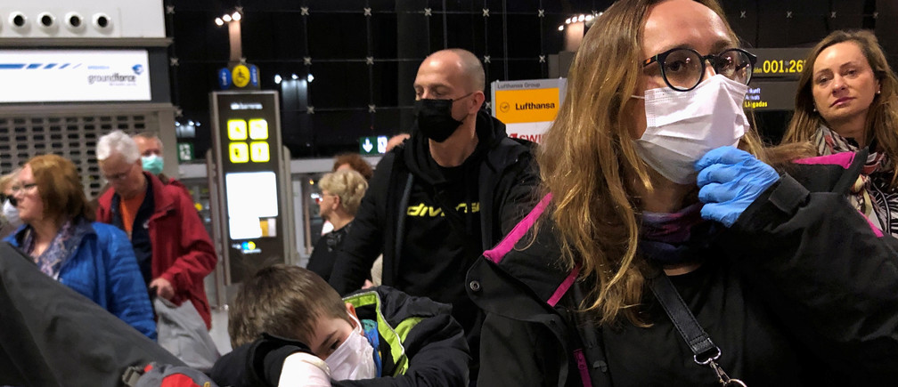 People wait for their flight as they wear protective mask against coronavirus (COVID-19) at the airport in Malaga, Spain March 17, 2020.