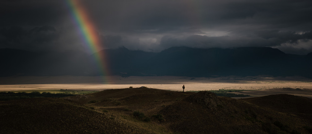 Breathtaking view of bright rainbow in dark sky with overcast above green mountain valley.