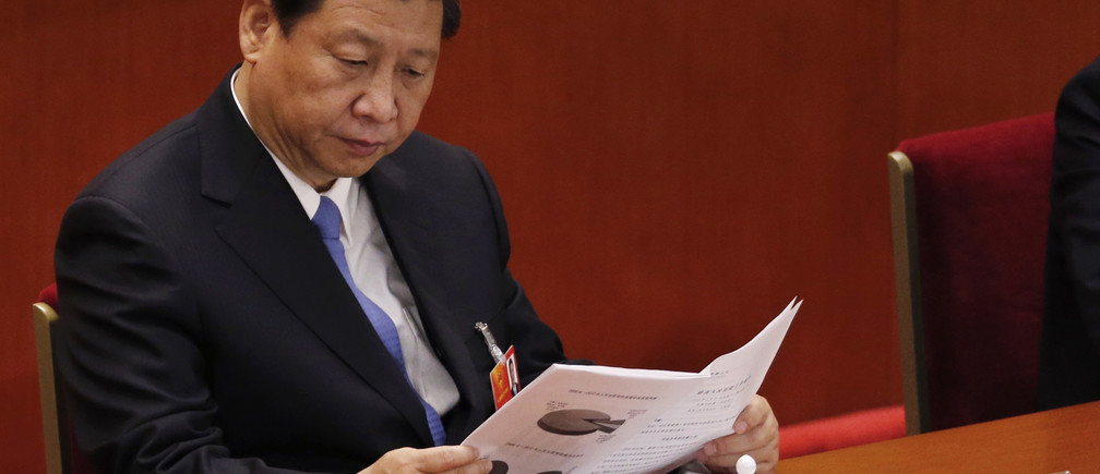 China's Communist Party Chief Xi Jinping reads at the Great Hall of the People during the third plenary session of the National People's Congress (NPC) in Beijing March 10, 2013.