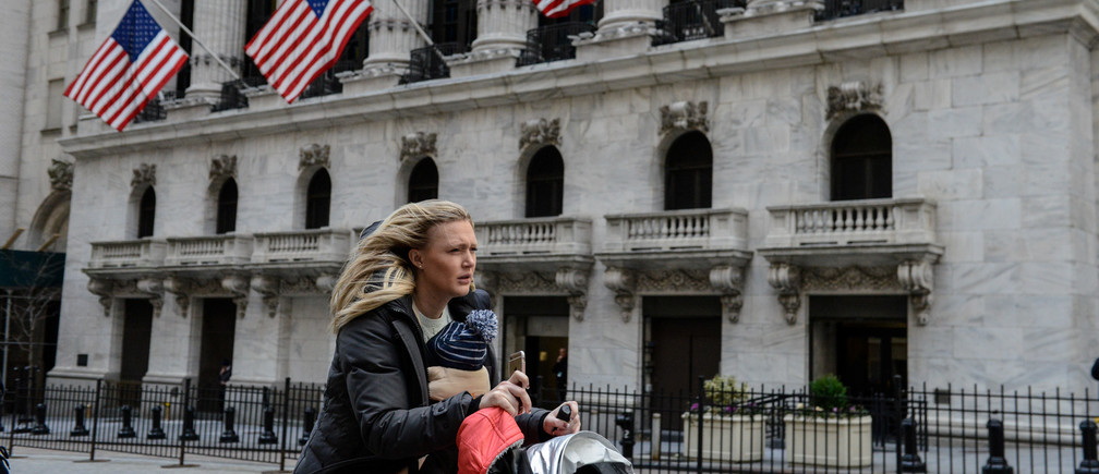A woman pushes a stroller past the New York Stock Exchange on a windy day in New York City, U.S. February 13, 2017. REUTERS/Stephanie Keith - RC1F88463F80