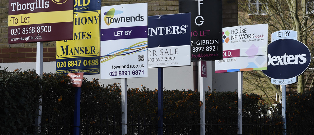 Property estate agent sales and letting signs are seen attached to railings in London, Britain, March 30, 2016. REUTERS/Toby Melville - RTSCYRG