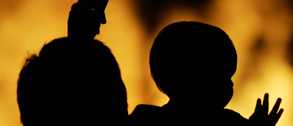 A parent holds their child as they watch a bonfire during the traditional San Juan's (Saint John) night in Paredes, northern Spain June 24, 2007. Fires are lit throughout Spain on the eve of Saint John where people burn objects they no longer want and make wishes as they jump through the flames. REUTERS/Miguel Vidal (SPAIN) - GM1DVNZJTNAA