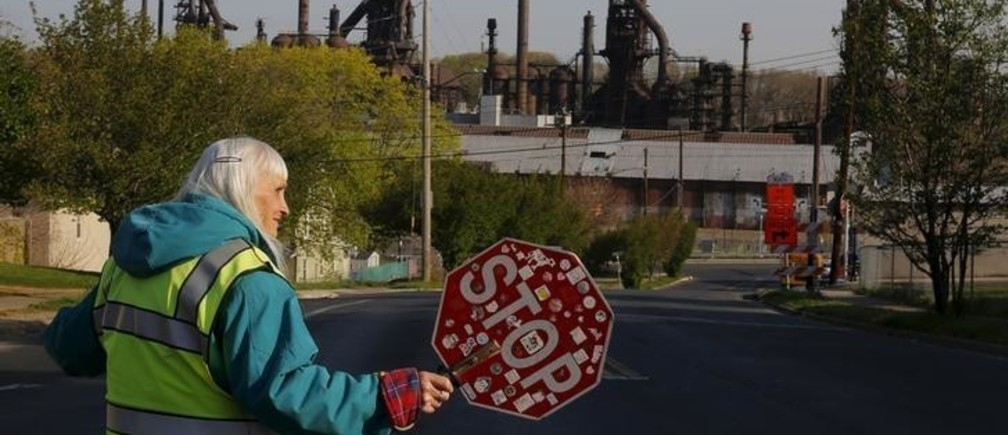 "Seventy-six-year-old crossing guard June Young helps pedestrians through an intersection she has worked for 32 years, with the blast furnaces from the now-closed Bethlehem Steel mill behind her, in Bethlehem, Pennsylvania, U.S. April 21, 2016. Young's father and two brothers all worked at the steel mill, her father from the age of eighteen until he retired at the age of sixty-two.   REUTERS/Brian Snyder    SEARCH ""BETHLEHEM STEEL"" FOR THIS STORY. SEARCH ""THE WIDER IMAGE"" FOR ALL STORIES"