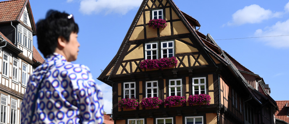 REFILE -  CLARIFYING INFORMATION A woman is seen in front of medieval half-timbered houses in UNESCO World Heritage Site of Quedlinburg, Germany, August 11, 2019. REUTERS/Annegret Hilse - RC123EE79A30