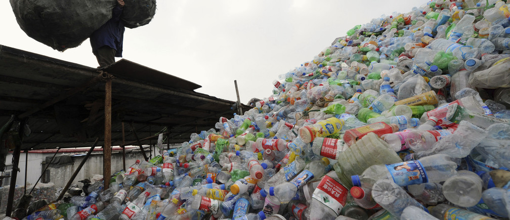 A man carries a bag of plastic bottles on a roof at a recycling centre in Hefei, Anhui province December 1, 2011.