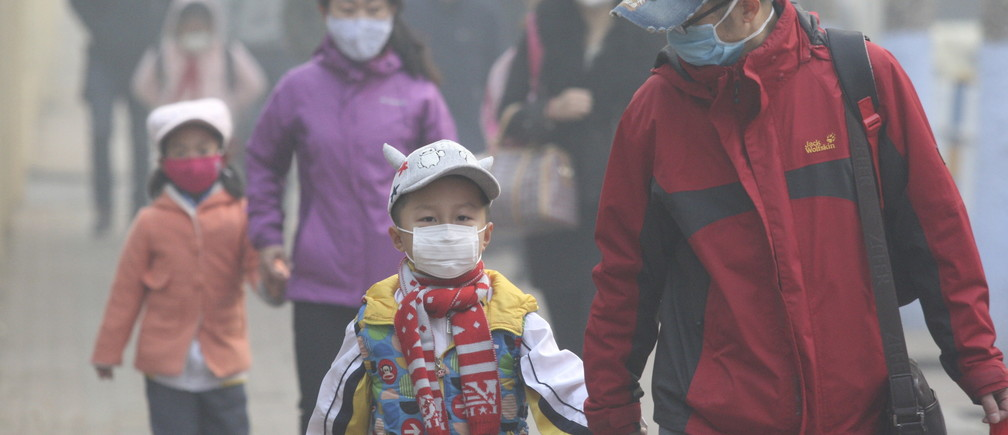 Young students and their parents wearing masks walk along a street on a hazy day in Harbin, Heilongjiang province, China, November 3, 2015. Some kindergartens and schools were closed as severe air pollution hit northeastern Chinese city of Harbin on Tuesday, local media reported. REUTERS/Stringer CHINA OUT. NO COMMERCIAL OR EDITORIAL SALES IN CHINA  - GF20000043621