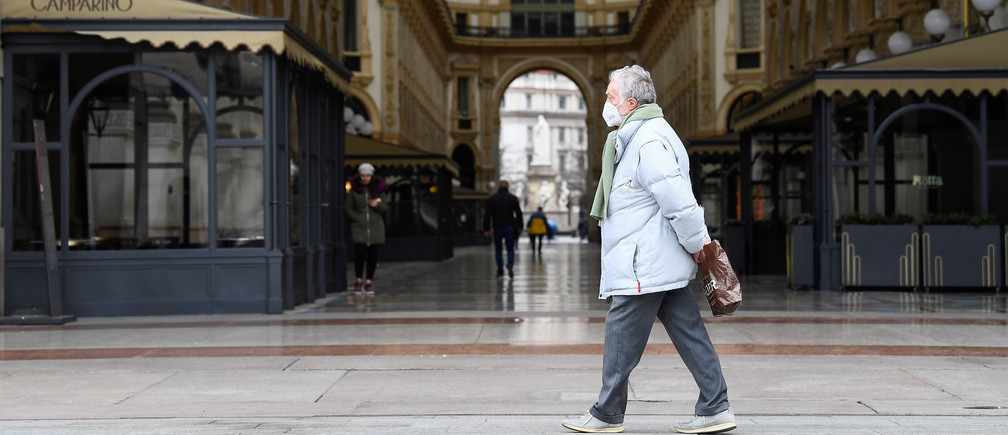 A man wearing a protective face mask walks past a deserted Galleria Vittorio Emanuele II, on the third day of an unprecedented lockdown across of all Italy imposed to slow the outbreak of coronavirus, in Milan, Italy, March 12, 2020. REUTERS/Flavio Lo Scalzo - RC2CIF9VQSD5