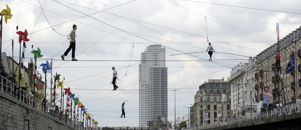 Tightrope walkers perform above a canal in Brussels April 26, 2014. Approximately forty-four tightrope walkers made an attempt to cross the canal during a performance.       REUTERS/Laurent Dubrule                  (BELGIUM - Tags: SOCIETY TPX IMAGES OF THE DAY) - RTR3MQ6J