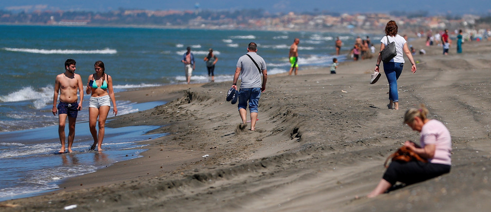 People enjoy the sunny weather on the Fregene beach, as Italy eases some of the lockdown measures put in place following the coronavirus disease (COVID-19) outbreak, in Fregene, near Rome, Italy, May 21, 2020. REUTERS/Guglielmo Mangiapane - RC2YSG9FD4S1