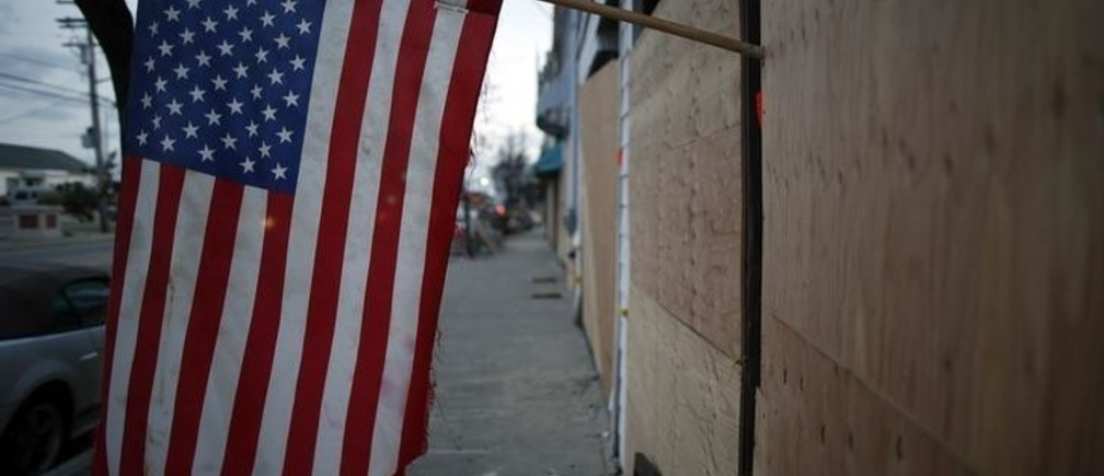 An American flag hangs on the front of a row of boarded up buildings, destroyed by flooding from the storm surge during Hurricane Sandy, in Sea Bright, New Jersey, November 15, 2012. REUTERS/Chip East (UNITED STATES - Tags: ENVIRONMENT)