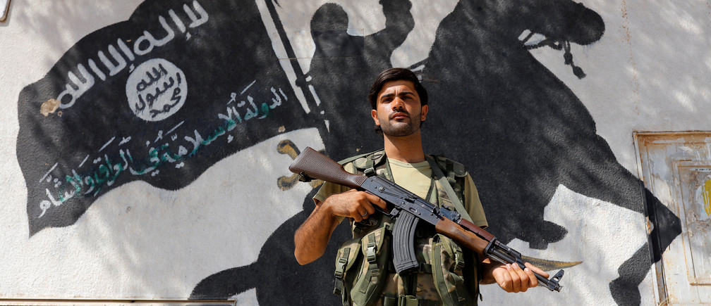 A member of Turkish-backed Free Syrian Army (FSA), seen with a mural of the Islamic State in the background, stands guard in front of a building in the border town of Jarablus, Syria, August 31, 2016. REUTERS/Umit Bektas TPX IMAGES OF THE DAY      - RTX2NQ4X