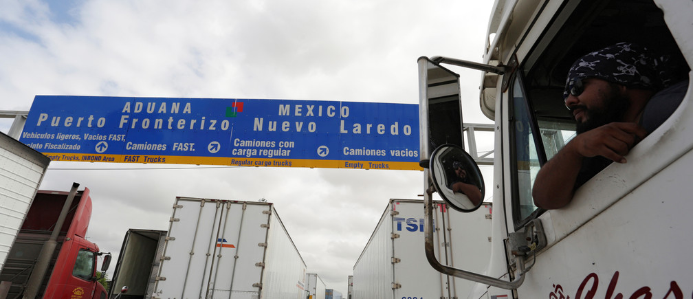 A driver leans out the cabin window while waiting in a queue for border customs control to cross into U.S. at the World Trade Bridge in Nuevo Laredo, Mexico, November 2, 2016.
