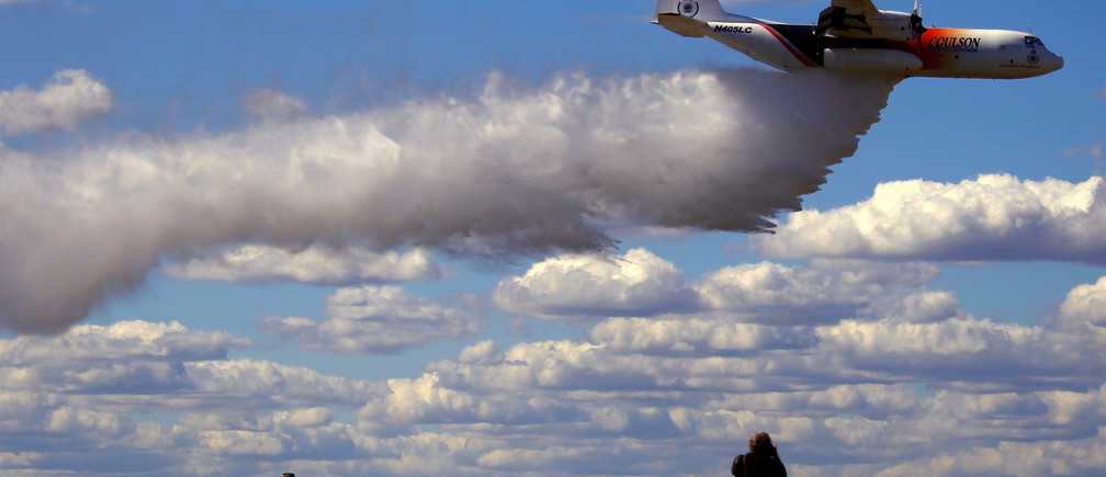Photographers take photographs of the Large Air Tanker (LAT) C-130 Hercules, also known as 'Thor', as it drops a load of around 15,000 litres during a display by the Rural Fire Service ahead of the bushfire season at RAAF Base Richmond  Sydney, Australia, September 1, 2017.  REUTERS/David Gray     TPX IMAGES OF THE DAY - RC1477FAFED0