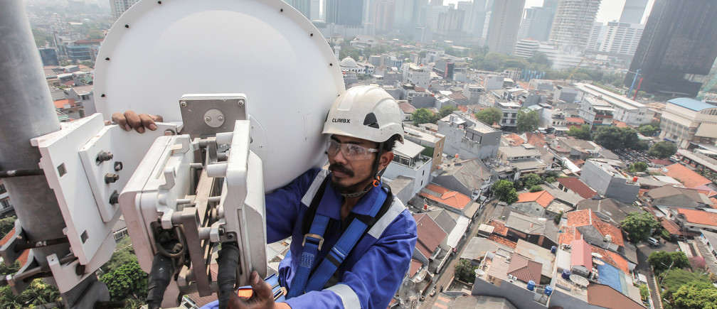 An XL Axiata technician checks the operator's base transceiver station on a tower in Jakarta, Indonesia, July 13, 2018. Antara Foto/Muhammad Adimaja/via REUTERS     ATTENTION EDITORS - THIS IMAGE WAS PROVIDED BY A THIRD PARTY. MANDATORY CREDIT. INDONESIA OUT. NO COMMERCIAL OR EDITORIAL SALES IN INDONESIA. - RC1B68FD27B0