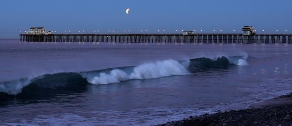 A Blue Moon comes out of a lunar eclipse as it sets past an ocean pier in Oceanside, California, U.S., January 31, 2018. REUTERS/Mike Blake