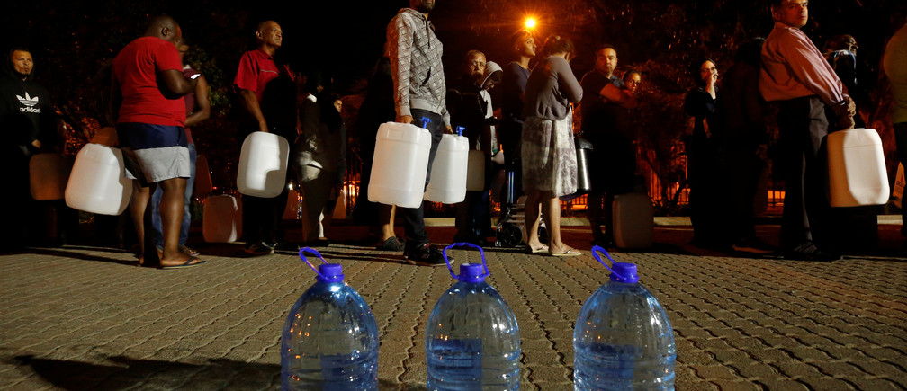People queue to collect water from a spring in the Newlands suburb as fears over the city's water crisis grow in Cape Town, South Africa, January 25, 2018. Picture taken January 25, 2018. REUTERS/Mike Hutchings - RC1B43915CB0