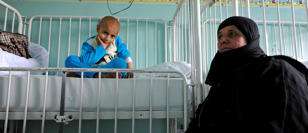 "Syrian girl Rahma (L) sits on a bed next to her grandmother Um Ahmad, as she receives treatment for cancer at Damascus Children's Hospital in Damascus, Syria, March 16, 2017. REUTERS/Omar Sanadiki             SEARCH ""CANCER CHILDREN"" FOR THIS STORY. SEARCH ""WIDER IMAGE"" FOR ALL STORIES. - RC1FB34FFBE0"