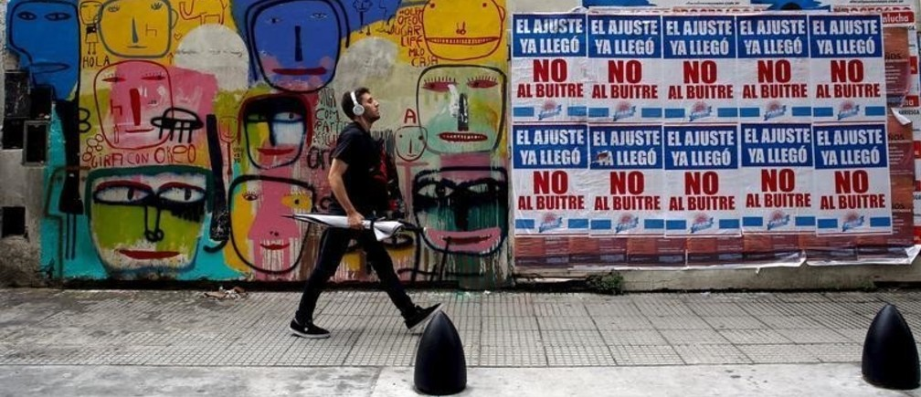 "A man walks by posters (R) against payment of Argentina's defaulted debt in Buenos Aires' financial district, Argentina, March 18, 2016. The posters read ""Austerity measures are already here, not to the vulture"" (many Argentines deride the holdout funds as ""vultures"").  REUTERS/Marcos Brindicci - GF10000350804"