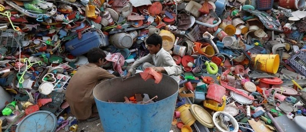 Two boys sort out plastic recyclables as they work in a yard in Peshawar, Pakistan November 19, 2018. REUTERS/Fayaz Aziz - RC17776866B0