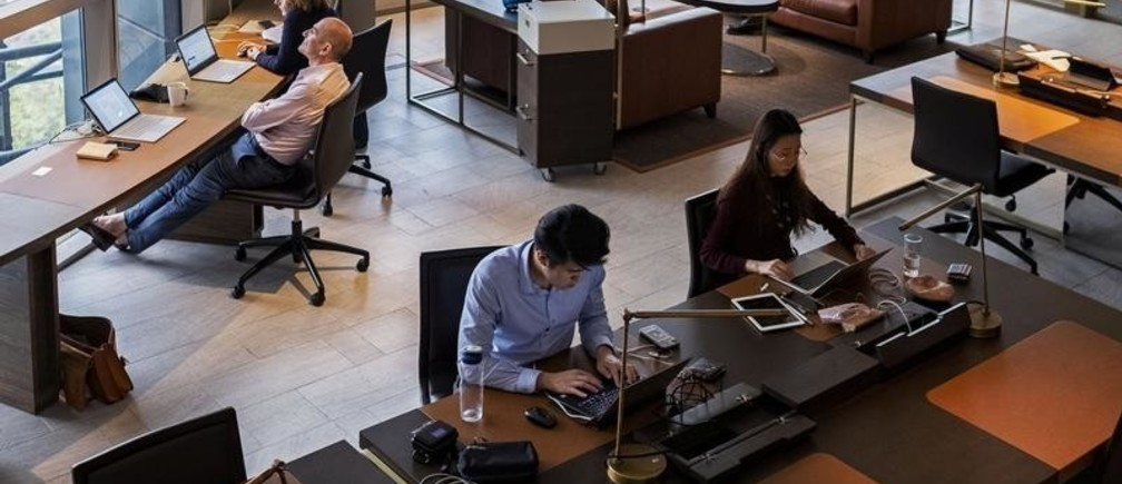 People sit at hot desks at co-working space The Great Room's Centennial Tower location in Singapore, July 2, 2019. Picture taken July 2, 2019. REUTERS/Loriene Perera - RC1DCAB68B80