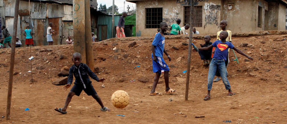 "A goalkeeper attempts to save the ball at a makeshift soccer pitch near Mathare valley slums in Nairobi, Kenya May 5, 2018. The eyes of the world will turn to Russia this week for the four-yearly gathering of soccer's superstars but it is away from the glitzy new stadiums built at a staggering cost you must look to find the sport's beating heart; to the dusty streets and poverty-wracked neighbourhoods where the simple act of scoring a goal can still transcend the grind of everyday life.    Picture taken May 5, 2018. REUTERS/Njeri Mwangi TO FIND ALL PICTURES SEARCH ""SOCCER-WORLDCUP/STREETGOALS\ - RC1A430F6420"