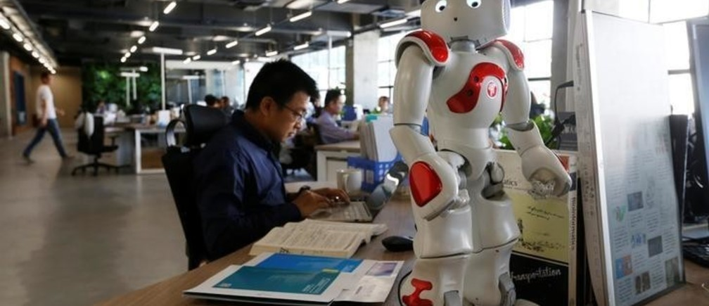 Staff work behind a robot at iCarbonX, a start up company focusing on combining genomics with other health factors to create a digitalized form of life, in Shenzhen, China May 25, 2018.   REUTERS/Bobby Yip