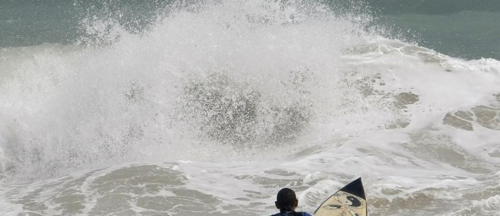 A surfer gets in the water at Condado beach to ride the 20 feet high waves due to a low pressure system in the North Atlantic Ocean in San Juan March 20, 2008. REUTERS/Ana Martinez (PUERTO RICO) - GM1E43L0IY401