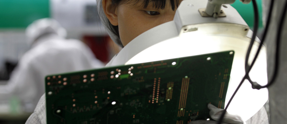 A worker examines a circuit board inside a Foxconn factory in the township of Longhua in the southern Guangdong province May 26, 2010. A spate of nine employee deaths at global contract electronics manufacturer Foxconn, Apple's main supplier of iPhones, has cast a spotlight on some of the harsher aspects of blue-collar life on the Chinese factory floor.   REUTERS/Bobby Yip  (CHINA - Tags: BUSINESS EMPLOYMENT) - GM1E65Q1AHV01