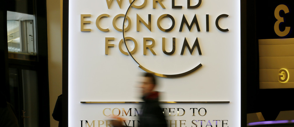 A man walks past the official logo of the World Economic Forum (WEF) inside the Congress Hall at the Swiss Alpine resort of Davos January 22, 2013. The annual World Economic Forum held from January 23 to 27, 2013 in Davos. REUTERS/Pascal Lauener (SWITZERLAND - Tags: POLITICS BUSINESS) - BM2E91M0Y9Q01