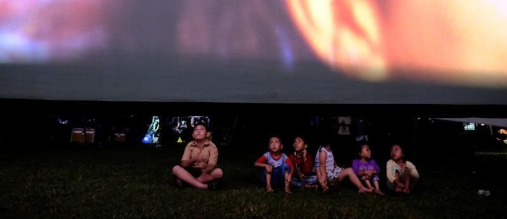 """Children sit in a soccer field watching films, during a wedding party in Tangerang, Indonesia, April 15, 2017. REUTERS/Beawiharta  SEARCH """"BEAWIHARTA CINEMA"""" FOR THIS STORY. SEARCH """"WIDER IMAGE"""" FOR ALL STORIES.  TPX IMAGES OF THE DAY. - RC119703BB70"""
