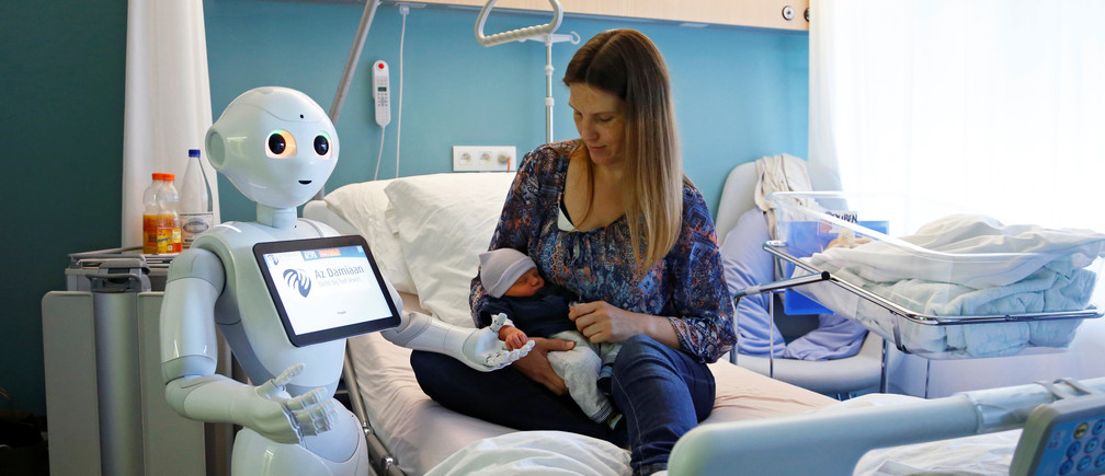 """New recruit """"Pepper"""" the robot, a humanoid robot designed to welcome and take care of visitors and patients, holds the hand of a new born baby next to his mother at AZ Damiaan hospital in Ostend, Belgium June 16, 2016. REUTERS/Francois Lenoir     TPX IMAGES OF THE DAY      - D1AETKFZXJAA"""