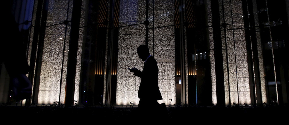 A pedestrian holding a mobile phone walks on a street at a business district in Tokyo, Japan, December 14, 2015. Japanese business confidence held steady and companies maintained their bullish spending plans, a quarterly central bank survey showed on Monday, offering some relief to policymakers worried that global headwinds could upset a fragile economic recovery. REUTERS/Yuya Shino - GF10000265186