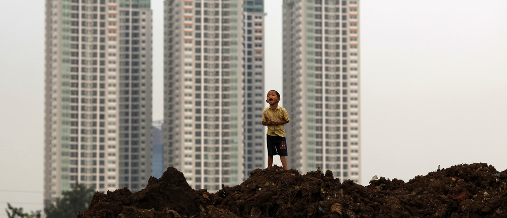 A child stands near a new apartment complex in Jakarta July 9, 2009. Indonesia's President Susilo Bambang Yudhoyono said on Thursday, a day after his landslide re-election, that he would spur growth in Southeast Asia's biggest economy to a target of 4-4.5 percent in 2009 as interest rates fall to 6 percent by year-end. REUTERS/Beawiharta (INDONESIA POLITICS ELECTIONS) - RTR25HEX