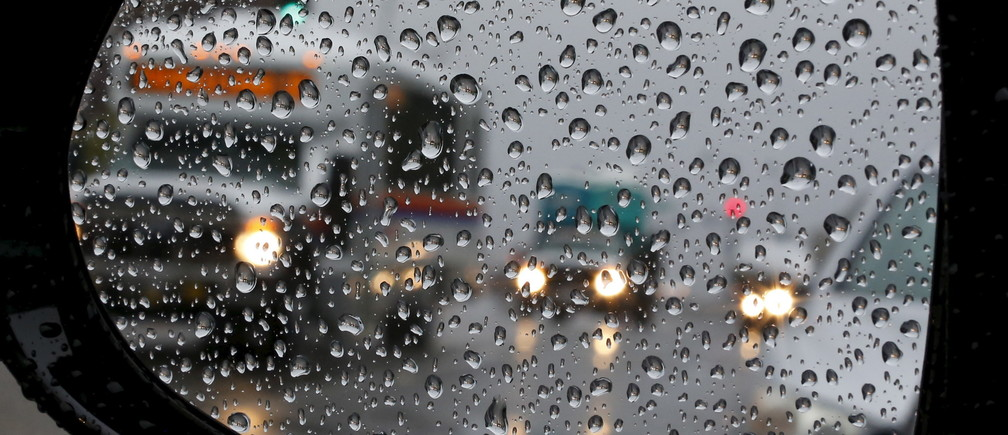 Traffic is reflected in a car mirror as heavy rain falls in San Juan Capistrano, California September 15, 2015.