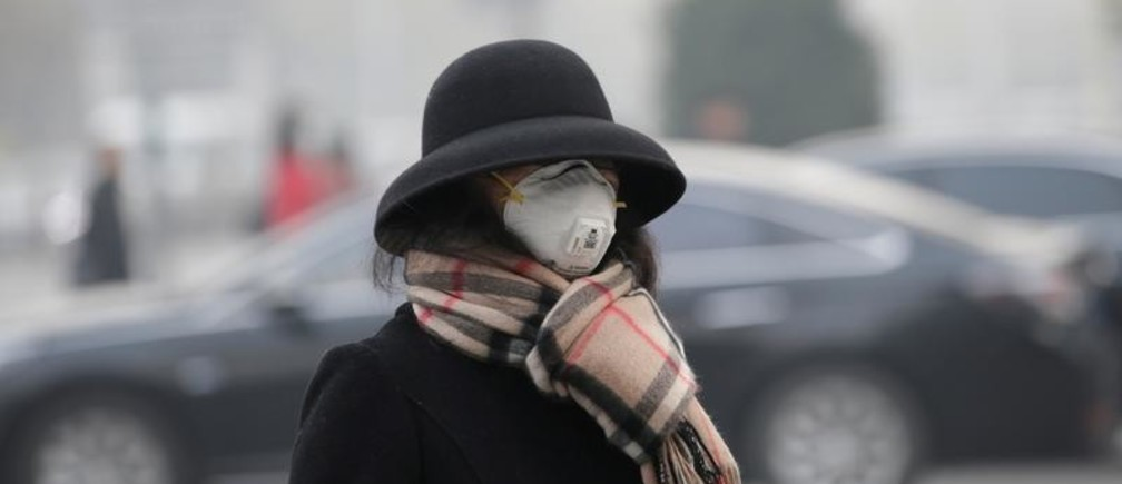 A woman wearing a mask walks on a road as heavy smog blankets China's capital after the city issued its first air pollution alert for the winter season, in Beijing, China November 26, 2018. REUTERS/Jason Lee - RC1F860B3440
