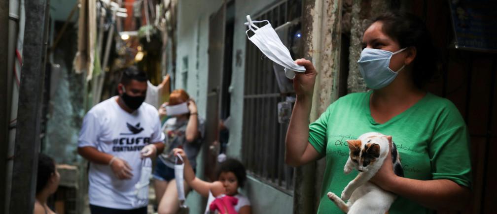 Una mujer agita una máscara facial protectora dada por miembros de la Central Unica das Favelas (CUFA), una organización no gubernamental brasileña, en medio del brote de la enfermedad coronavirus (COVID-19) en la favela de Heliópolis en Sao Paulo, Brasil, el 18 de junio de 2020.