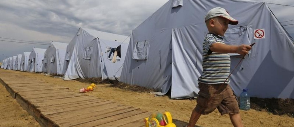 Alexander, 4, walks with a toy at a temporary tent camp set up for Ukrainian refugees outside Donetsk, located in Russia's Rostov region near the Russian-Ukrainian border, August 18, 2014.