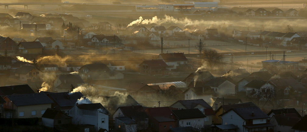 Smoke rises from the chimneys of houses during sunrise in Slavonski Brod, Croatia February 11, 2016