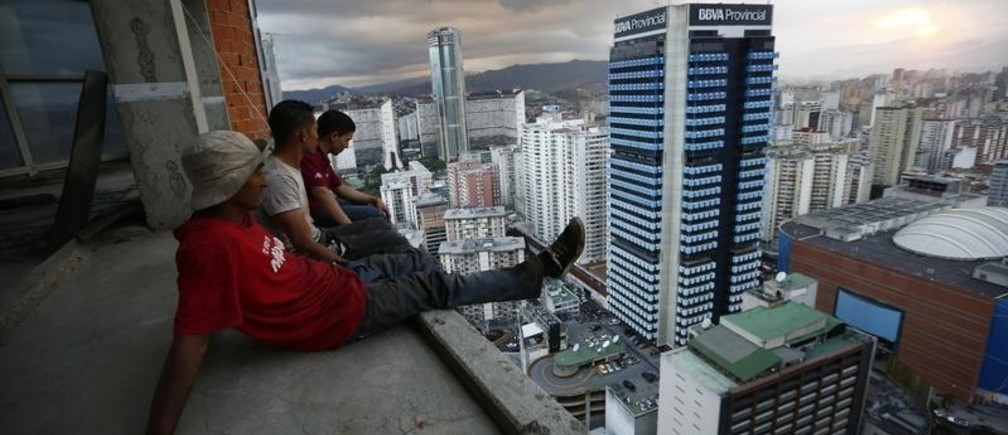 """Men rest after salvaging metal on the 30th floor of the """"Tower of David"""" skyscraper in Caracas February 3, 2014. It boasts a helicopter landing pad, glorious views of the Avila mountain range, and large balconies for weekend barbecues. Yet a 45-storey skyscraper in the center of Venezuela's capital Caracas is no five-star hotel or swanky apartment block: it is a slum, probably the highest in the world. Dubbed the """"Tower of David"""", the building was intended to be a shining new financial center but was abandoned around 1994 after the death of its developer - banker and horse-breeder David Brillembourg - and the collapse of the financial sector. Squatters invaded the huge concrete skeleton in 2007, then-president Hugo Chavez's socialist government turned a blind eye, and now about 3,000 people call the tower their home. Picture taken February 3, 2014. REUTERS/Jorge Silva (VENEZUELA - Tags: BUSINESS SOCIETY POVERTY TPX IMAGES OF THE DAY) - GM1EA420Q7R01"""