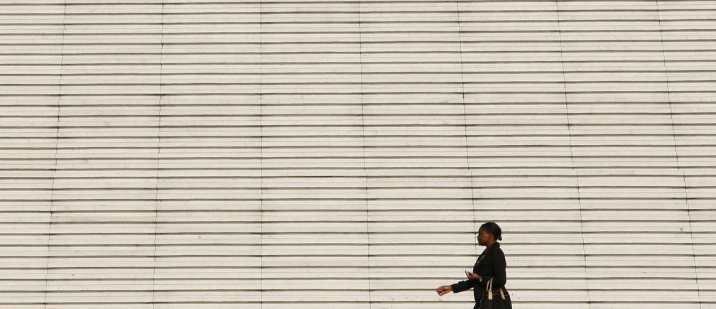 businesswoman walks past the steps at the Arche de la Defense, the financial and business district west of Paris.