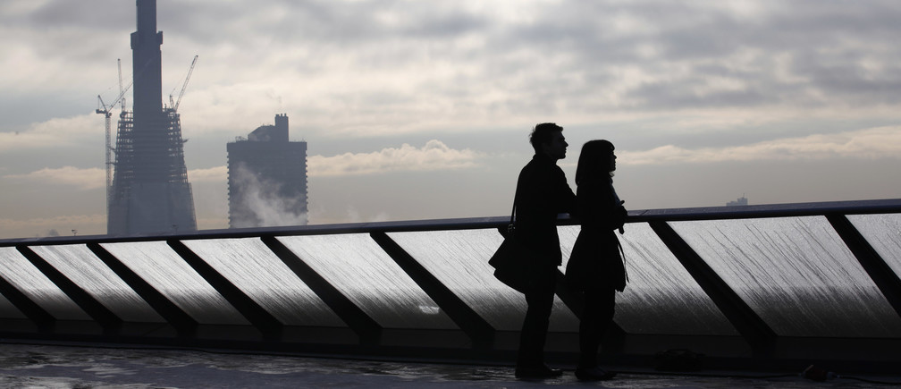 Construction takes place on The Shard building (at rear) as visitors pose on the balcony at One New Change shopping mall in London November 16, 2010. REUTERS/Suzanne Plunkett (BRITAIN - Tags: CITYSCAPE BUSINESS CONSTRUCTION) - RTXUPK5