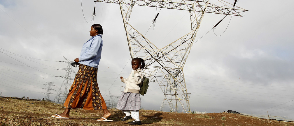 A woman walks her child to school past high voltage electrical pylons on the outskirts of Kenya's capital Nairobi, March 14, 2011. A union representing workers at Kenya's sole power supplier started on Monday a strike to protest unfair employment terms, its secretary general said. Kenya power has been involved in a protracted dispute with Kenya Electrical Trade and Allied Workers Union (KETAWU), which claims that more than a third of workers are on casual terms, in violation of the country's labour law. REUTERS/Thomas Mukoya (KENYA - Tags: BUSINESS ENERGY EMPLOYMENT) - GM1E73E1N5L01