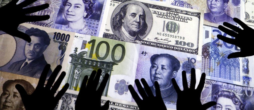 Hands are silhouetted against a backdrop projected with the picture of various currencies of money in this illustration taken April 4, 2016.