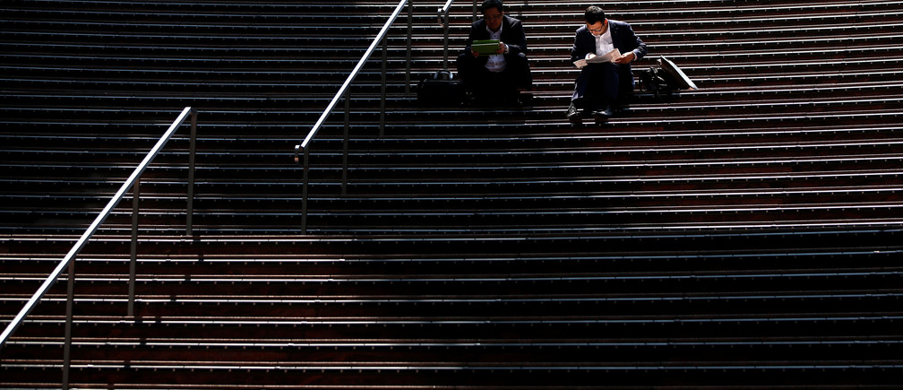 Businessmen using tablet computers sit on steps at Kyoto station in Kyoto, Japan May 11, 2017. REUTERS/Issei Kato - RTS164WE