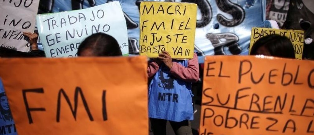 """People hold placards as they attend a demonstration against economic measures of Argentine President Mauricio Macri's government, in Buenos Aires, Argentina September 24, 2019. The placards read: """"IMF"""",""""IMF the adjustment"""", """"The people suffer poverty"""", """"Enough"""" and """"Genuine work"""". REUTERS/Agustin Marcarian - RC118FBA70B0"""