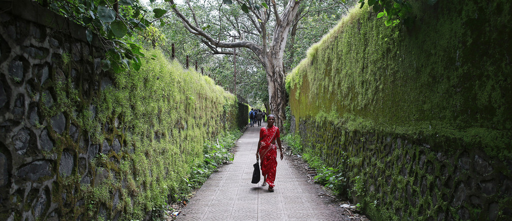 A woman commuter walks on a pathway next to a railway station in central Mumbai September 17, 2014. REUTERS/Danish Siddiqui (INDIA - Tags: SOCIETY) - GM1EA9H1MXK01