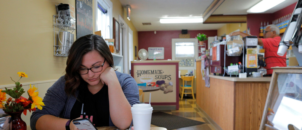 Carlee Giordano looks at her mobile phone at the Morning Emporium Coffee House in Precinct 7, where the vote was split 876/876 between Donald Trump and Hillary Clinton in 2016, in Saginaw Township, Michigan, U.S., October 11, 2019.  Picture taken October 11, 2019.     REUTERS/Brian Snyder - RC179E52A8E0