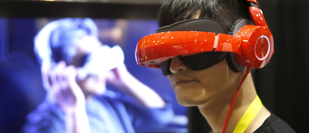 """Eric Yu of Royole models the company's foldable Smart Mobile Theater system during """"CES Unveiled,"""" a preview event of the 2016 International CES trade show, in Las Vegas, Nevada January 4, 2016. The $700.00 system has noise-canceling headphones and a viewing system that is vision correctable so you don't need to wear your glasses, Yu said."""